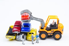 Miniature tiny toys doing business about cemetery car was damage. D by a car accident and old cars.Detail of industrial crane claw grabbing old car for recycling Stock Image