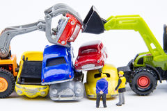 Miniature tiny toys doing business about cemetery car was damage. D by a car accident and old cars.Detail of industrial crane claw grabbing old car for recycling Royalty Free Stock Photos