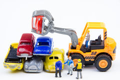 Miniature tiny toys doing business about cemetery car was damage. D by a car accident and old cars.Detail of industrial crane claw grabbing old car for recycling Royalty Free Stock Photography