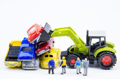 Miniature tiny toys doing business about cemetery car was damage. D by a car accident and old cars.Detail of industrial crane claw grabbing old car for recycling Royalty Free Stock Images