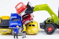 Miniature tiny toys doing business about cemetery car was damage. D by a car accident and old cars.Detail of industrial crane claw grabbing old car for recycling Royalty Free Stock Photo