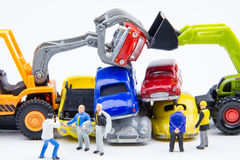 Miniature tiny toys doing business about cemetery car was damage. D by a car accident and old cars.Detail of industrial crane claw grabbing old car for recycling Royalty Free Stock Image