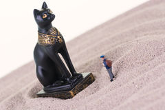 Miniature tourist with the Egyptian guardian Bastet statue Stock Photo