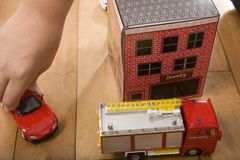 Miniature town. A child holding on to a red toy car, moving it through a miniature town with a building and a fire engine Royalty Free Stock Photos
