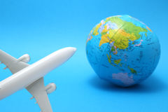 Miniature toy airplane and globe on blue background. Stock Image