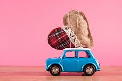 Miniature toy car carrying retro heart on pink background royalty free stock photos