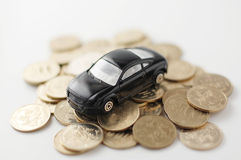Miniature toy car on pile of money. Miniature toy car Royalty Free Stock Photo