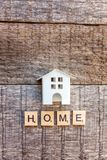 Miniature toy model house with inscription HOME letters word on wooden background. Miniature toy model house with inscription HOME letters word on wooden royalty free stock images