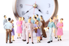 Miniature toy people stand near alarm clock Stock Images