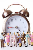 Miniature toy people stand near alarm clock Royalty Free Stock Photos