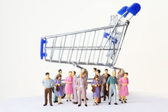 Miniature toy people stand near shopping cart Stock Image