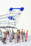 Miniature toy people stand near shopping cart Stock Photos