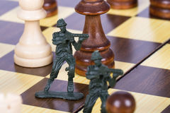 Miniature Toy Soldiers on Chess Board Royalty Free Stock Images