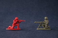 Miniature toy soldiers fighting. Plastic toy military men models attack at war. Miniature toy soldiers fighting. Red and green plastic toy military men models royalty free stock photos