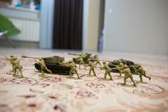 Miniature toy soldiers and tank on board. Close up image of toy military at war. Selective focus stock photography