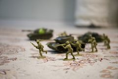 Miniature toy soldiers and tank on board. Close up image of toy military at war. Selective focus stock image
