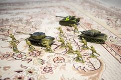 Miniature toy soldiers and tank on board. Close up image of toy military at war. Selective focus royalty free stock photo