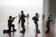 Miniature toy soldiers and tank on board. Close up image of toy military at war. Selective focus stock photo