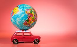 Miniature Toy vintage car carrying a world map balloon.Travel and transport concept. stock photography