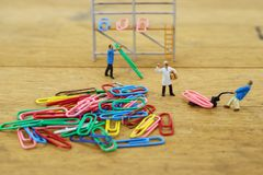 Miniature toy workers carry a paper clip. The concept of a collective solution to any problem. Workers perform disposal of the Chief. Close-up view stock photos