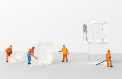 Miniature toy workers crash the ice for cold drinks. The concept of a collective solution to any problem. Miniature toy workers crash the ice for cold drinks royalty free stock photos