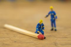 Miniature toy workers with matches stock images