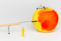 Miniature toy workers paint the apple. Royalty Free Stock Photos
