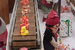 Miniature toys on conveyor belt in shopping center
