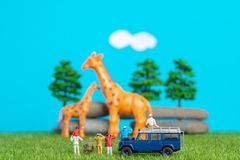 Miniature toys of a group of people on safari trip watching giraffes - a hunter, father and son on shoulder ride, photographer royalty free stock images