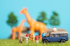 Miniature toys of a group of people on safari trip watching giraffes - a hunter, father and son on shoulder ride, photographer royalty free stock photography