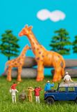 Miniature toys of a group of people on safari trip watching giraffes - a hunter, father and son on shoulder ride, photographer stock image