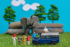 Miniature toys of a group of people on safari trip watching loxodonta african elephant - a hunter, father and son on shoulder ride stock images