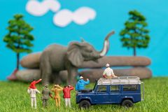 Miniature toys of a group of people on safari trip watching loxodonta african elephant - a hunter, father and son on shoulder ride stock photo