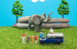 Miniature toys of a group of people on safari trip watching loxodonta african elephant - a hunter, father and son on shoulder ride stock image