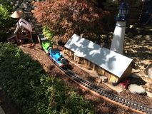 Miniature train display. Hey miniature train display featuring a train station, lighthouse, barn, greenery, rocks and Thomas the train on a track. Kids love Stock Photo