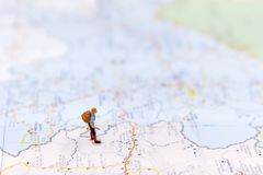 Miniature traveler with backpack standing on wold map for travel around the world. Stock Photography