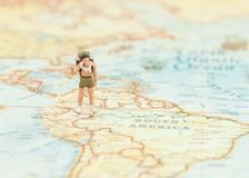 Miniature traveler man with backpack standing on wold map for travel around the world. royalty free stock image