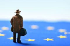 Miniature traveler man and european union flag. Miniature traveler man seen from behind wearing a hat and carrying a suitcase, on an european union flag Royalty Free Stock Photography