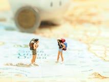 Miniature traveler saving money in piggy for travel royalty free stock photos