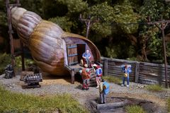 Miniature travelers standing at snail house stock photos