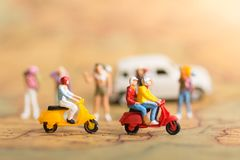 Miniature Travelers with two motorbikes. Drive through the front of backpackers on world map, using as a travel business concept.  Royalty Free Stock Image