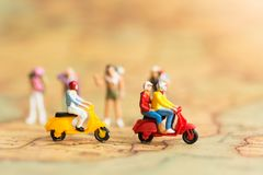 Miniature travelers with two motorbikes. Drive through the front of backpackers on world map, using as a travel business concept.  Royalty Free Stock Photography