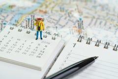 Miniature traveller, backpacker man figure standing on calendar stock photography