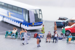 Miniature travellers at a busy bus station Royalty Free Stock Image