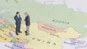 Miniature two businessman shakehand on china map. Man stock photo