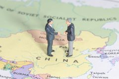 Miniature two businessman shakehand on china map. Man stock images