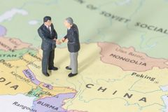 Miniature two businessman shakehand on china map. Man royalty free stock images