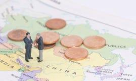 Miniature two businessman shakehand on china map. Man royalty free stock photo