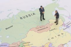 Miniature two businessman shakehand on china and russian map. Man royalty free stock photos