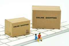 Miniature two people sitting on white keyboard Online shopping w royalty free stock photography